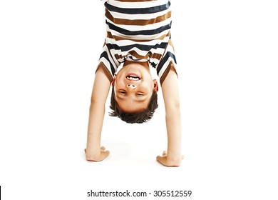 A kid upside down smiling to the camera.  Isolated on white background