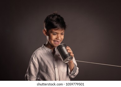 kid using a can as telephone on a gray background