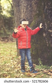 Kid using a DIY virtual reality cardboard headset outdoors. (Toned image)