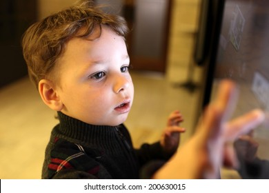 Kid using interactive touch screen in a museum