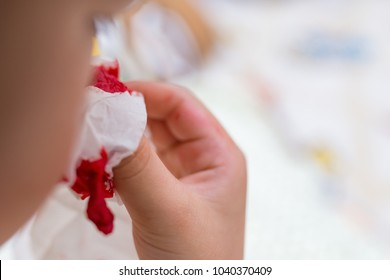 kid using tissue to stop the nose bleeding