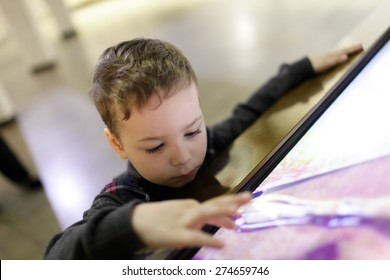 Kid using touch screen in the museum