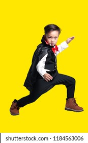 Kid of Vampire Halloween Concept. Portrait of a funny asian boy (6 year old) in vampire costume making a gesture to look awesome, acting to the camera with isolate yellow background and clipping path.