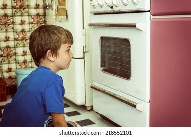 kid in a vintage kitchen looking if the cookies are ready,vintage filter added