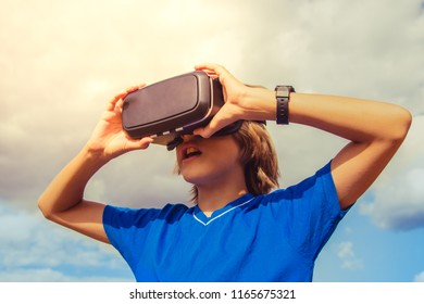 The kid with virtual reality glasses on the background of the cloudy sky. Virtual reality. 3D technology.