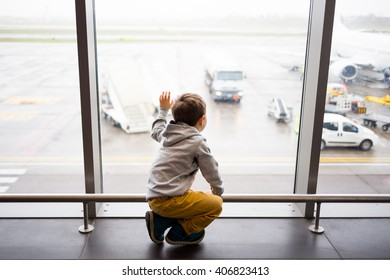 kid waiting in the airport terminal looking out the window to the planes