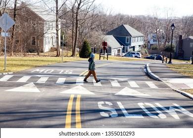 kid walking on crosswalk. boy goes across the road in front of the car