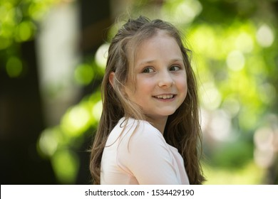 Kid walking sunny day. Emotional kid in park nature background. Young girl in park. Happy Lifestyle portrait of a beautiful young model girl with a sweet smile