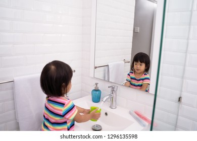 kid wash her mouth or gargle after brush her own teeth in the sink