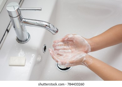 Kid washing hands in a white basin with a bar of white soap
