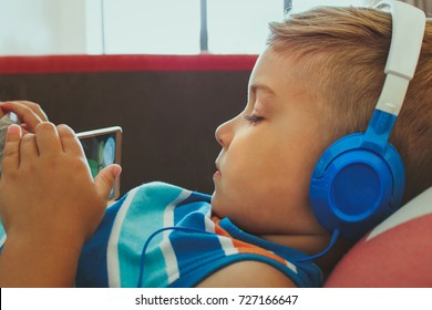 Kid watching cartoons on smart phone. Little boy with headphones watching movie on the internet.