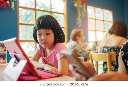 Kid watching tablet on the food table, children addicted cartoon