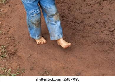 Kid wearing jeans trousers walking on muddy ground