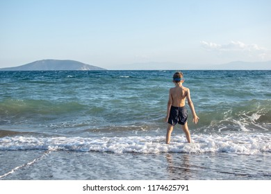 Kid wearing swimming goggles faces the wavy sea on a windy day.