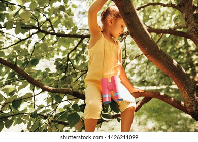 Kid wearing yellow romper, swinging on a tree brunch in the summertime in the park. Adorable blond little girl playing at nature background. Little explorer child having fun outdoors in the forest.