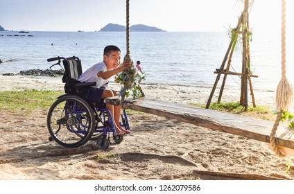 Kid in a wheelchair trying to catch a swing at the seaside.