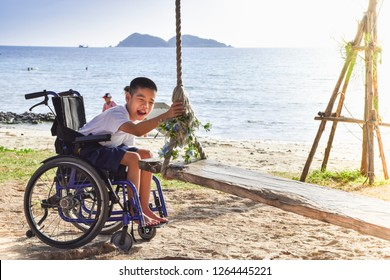 A Kid in a wheelchair trying to catch a swing at the seaside.