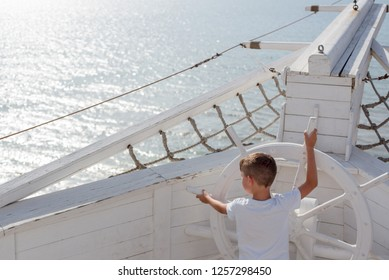 The kid in a white T-shirt holds the steering wheel of a large sailing white wooden old ship like a captain on the background of the sea.