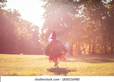 Kid in the witch suit.  Little girl in Halloween suit running trough park.