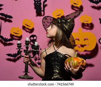 Kid in witches costume holds pumpkin and chandelier. Girl with proud face on pink background with bats and pumpkins decor. Little witch wearing black hat. Halloween party and decorations concept