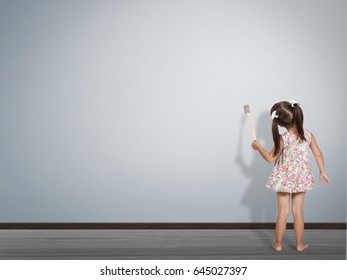 kid write with paint brush on blank wall, back view