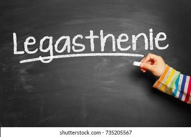 "Kid writes german word ""Legasthenie"" (dyslexia) on blackboard at school"
