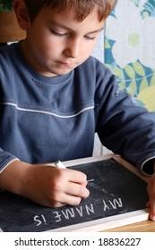 Kid writing on a blackboard