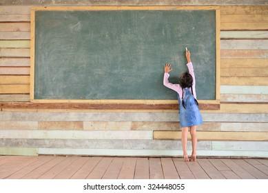 Kid writing on the old green chalkboard; Old wood wall