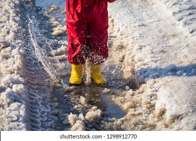 Kid in yellow rainboots jumping in the ice puddle with melting snow at sunny spring day, outdoors