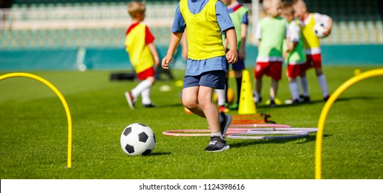 Kid Young Athletes Training with Football Equipment. Football Speed and Agility Training. Young Footballer in Blue Sportswear at Training Session on Grass Soccer Field