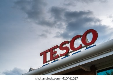 KIDDERMINSTER, UK - APRIL 2016: Tesco supermarket logo on top of store exterior against a moody sky
