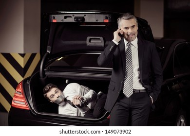 Kidnapped man. Tied up businessman lying in the car trunk and looking at camera while kidnapper talking at mobile phone