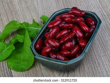 Kidney beans in the bowl with ruccola leaves on wood background