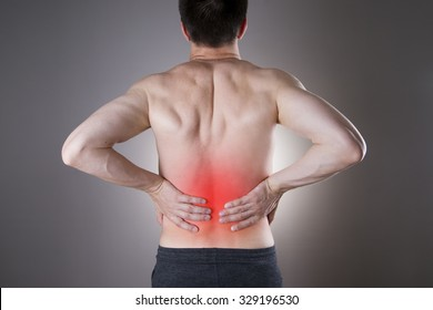 Kidney pain. Man with backache. Pain in the man's body on a gray background with red dot