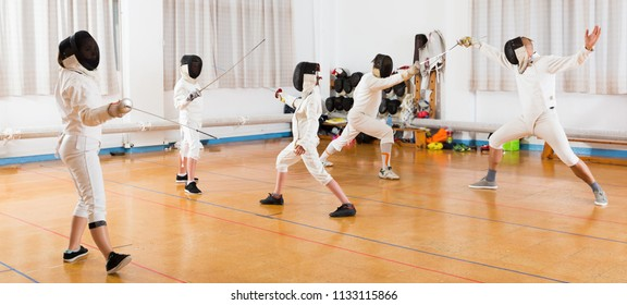 Kids with adults practicing effective fencing techniques in sparring in training room