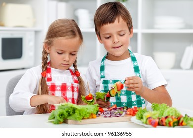 Kids with aprons preparing a healthy vegetables meal in the kitchen