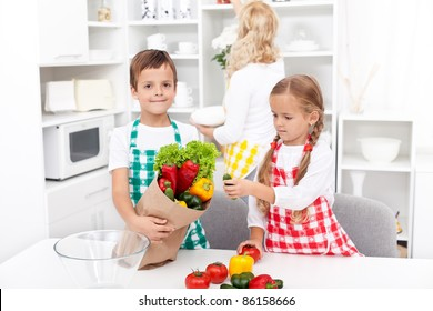 Kids with aprons unpacking groceries from paper bag in the kitchen