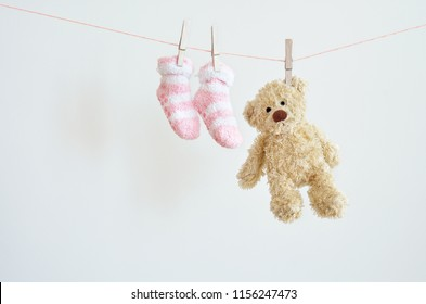 Kids background with pink baby socks and teddy bear with copy space