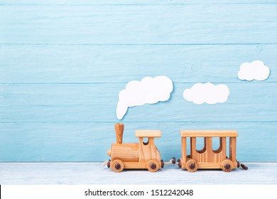 Kids background, toy wooden train with white paper steam on a blue wooden background
