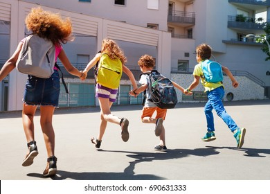 Kids with backpacks run to school