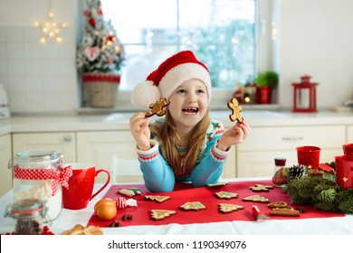 Kids bake Christmas cookies. Child in Santa hat cooking, decorating gingerbread man for Xmas celebration. Family preparing sweets in white kitchen with Christmas tree on snowy winter day.