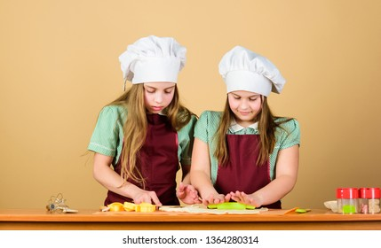 Kids baking cookies together. Kids aprons and chef hats cooking. Homemade cookies best. Family recipe. Cooking skill culinary education. Baking ginger cookies. Girls sisters having fun ginger dough.