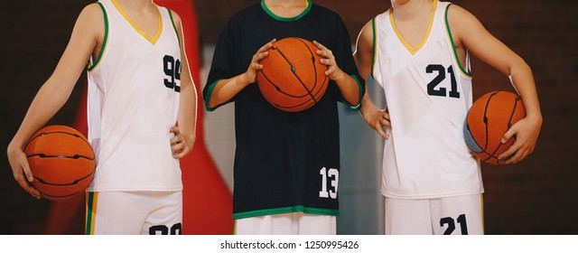 Kids Basketball Team. Young Basketball Players Holding Balls on Basketball Court. Basketball Horizontal Background with Blurred Background
