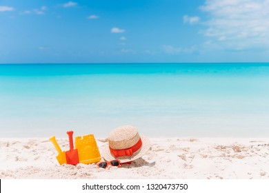 Kid's beach toys on white sandy beach background the sea