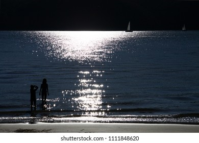 Kids at the beach watching a sail boat passing by