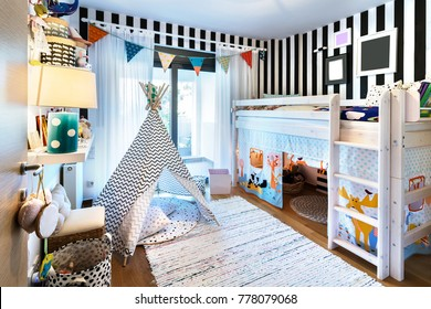 Kids bedroom  with bunk wooden bed, teepee, stands, carpet frames and toys.