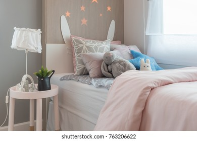 kid's bedroom with colorful pillows on bed with dolls and toys, interior design concept