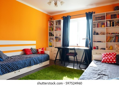 Kids bedroom in orange and blue colors with two beds and bookcases