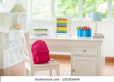 Kids bedroom with wooden desk and doll house. White sunny room with big window for young child. Home interior for little girl. Table for homework and study with lamp and abacus, books for school kid.