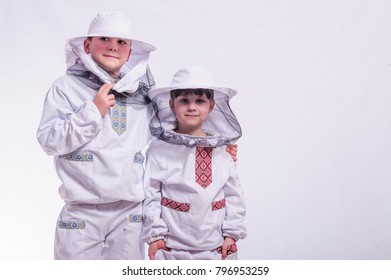 Kids in beekeeper's suits posing in studio white background.